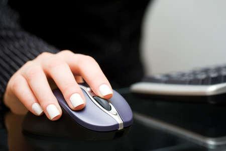 usando computadora: Mano femenina que sostiene el rat�n del ordenador