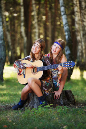 Hippie girls with guitar sitting on the stump photo