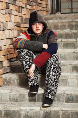 Young hippie man sitting on the steps photo