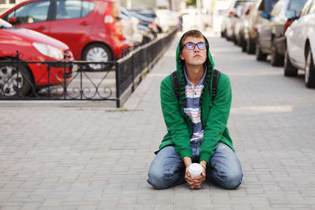 Young man sitting against a city traffic photo