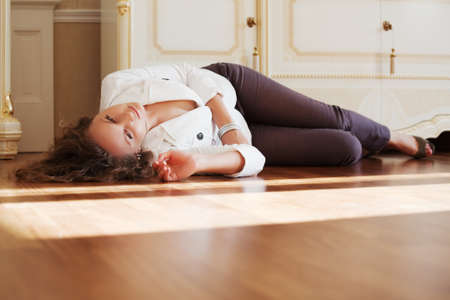 Beautiful woman lying on the parquet floor Stock Photo - 15921078
