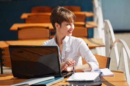obreros trabajando: Empresaria joven con ordenador port�til en un caf�