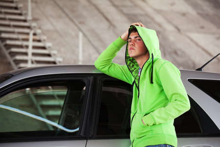 Young man standing against a car photo