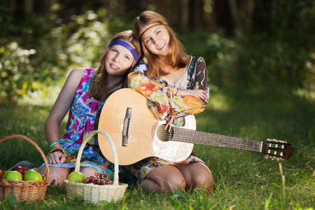 Hippie girls with a guitar outdoor photo