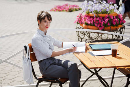 Young businesswoman at a sidewalk cafe Stock Photo
