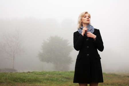 Young woman walking in an autumn foggy field Stock Photo - 16249355