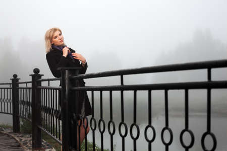 Young woman against a morning foggy landscape Stock Photo - 16409433