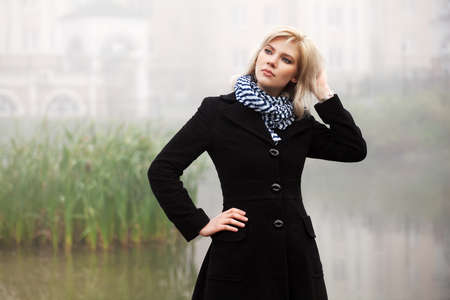 Young woman against a morning foggy landscape photo