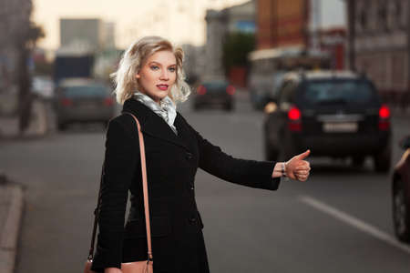 Young woman hailing a taxi cab