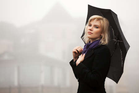 Young woman with umbrella in autumn foggy morning Stock Photo - 16483588