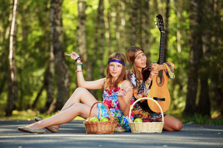 Hippie girls with guitar sitting on the road photo