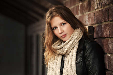 Teenage girl against a brick wall photo
