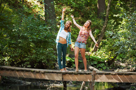 Happy young girls on the wooden bridge photo