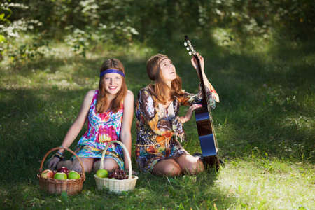 Hippie girls with a guitar in a forest photo