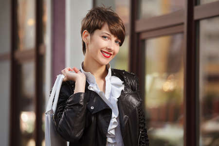 Happy young woman in leather jacket photo