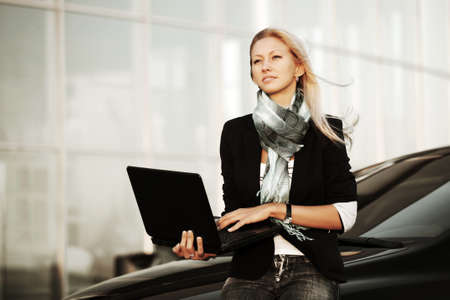 Young woman with laptop sitting on a car photo