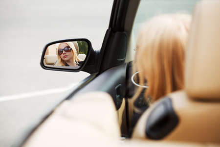 Young woman looking in the car mirror photo