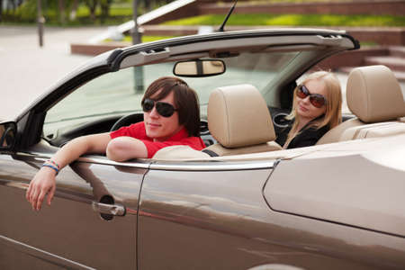 Young couple in a convertible car photo