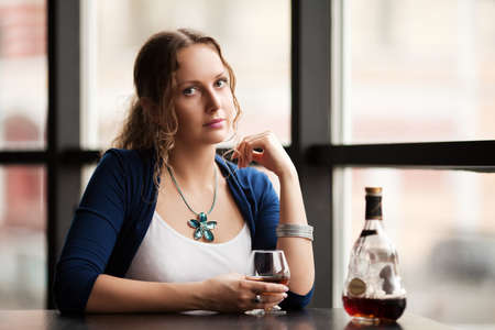 Beautiful young woman with cognac at restaurant photo