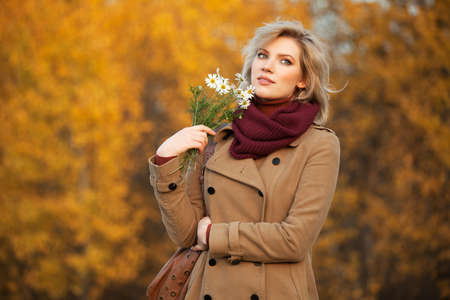 Young woman with a flowers in autumn forest photo