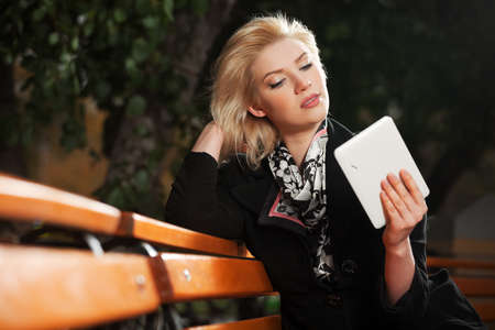 Blond woman holding a digital tablet computer photo