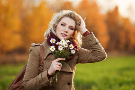 Young woman with a flowers in autumn field photo