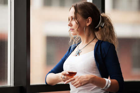 Beautiful young woman looking out the window photo