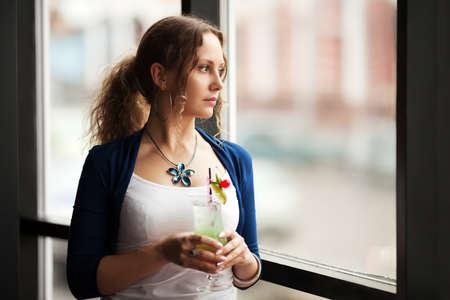 Mujer triste con el coctail mirando por la ventana Foto de archivo