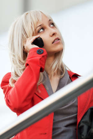 Young woman calling on the phone against office windows photo