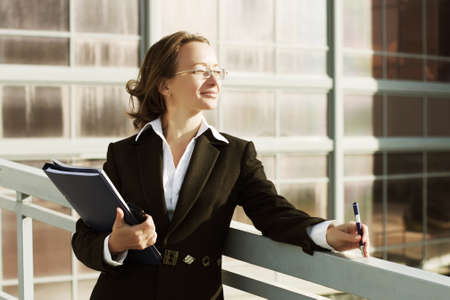 Businesswoman with a folder against industrial background photo