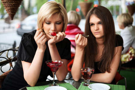 Two young women eating a dessert at sidewalk cafe photo