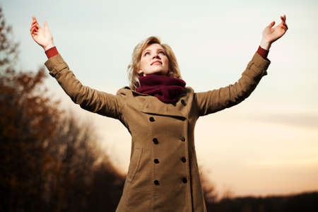 Woman with arms raised against a sky photo