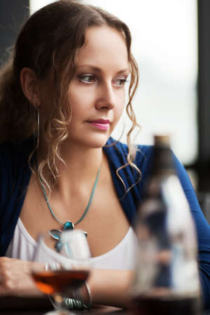 Beautiful young woman with cognac looking down photo