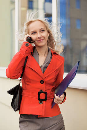 Young businesswoman with a folder calling on the phone photo