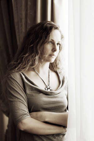 Sad beautiful woman looking out the window photo