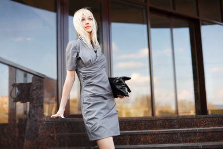 Young businesswoman on the steps against office windows Standard-Bild