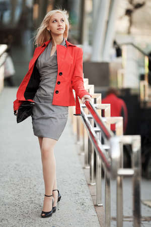 university life: Young businesswoman walking on the city street