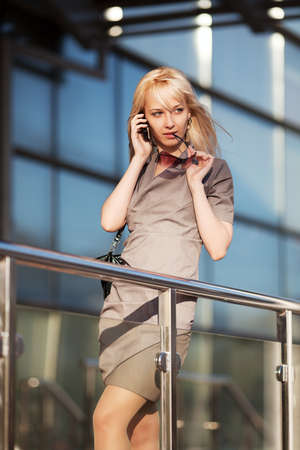 Blond woman calling on the phone against office windows photo