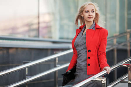 Young business woman walking on the city street photo