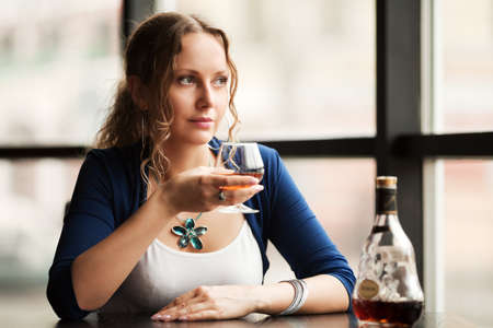 Beautiful young woman with cognac looking out the window photo