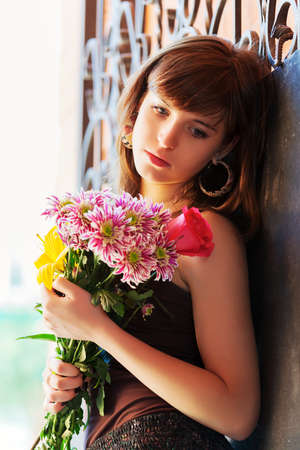 Sad young woman with a flowers photo