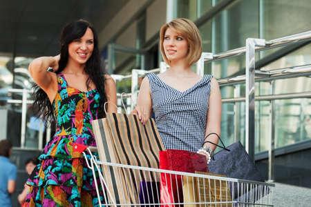 woman shopping cart: Two young women with shopping cart  Stock Photo