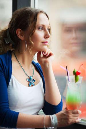 mirada triste: Joven y bella mujer mirando a trav�s de la ventana