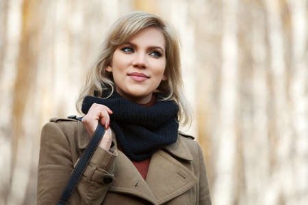 Happy blond woman in autumn forest photo