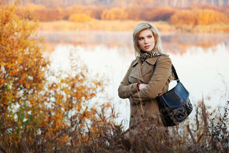 Blond woman against an autumn nature landscape photo