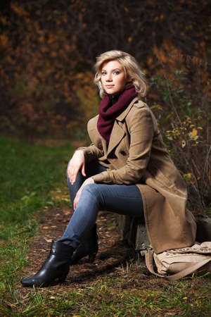 Young blond woman in autumn forest photo