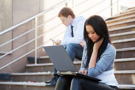 Young woman using laptop on the steps photo