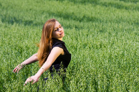 Happy young woman walking in a field photo