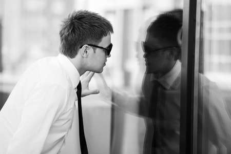 Young businessman looking through a window