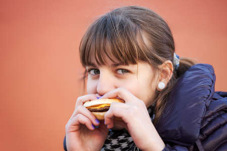 Teenage girl eating a burger photo